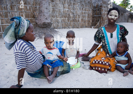 TWO YOUNG MAKUA MOTHERS WITH THEIR CHILDREN SITTING BESIDE A HUT ON THE BEACH OF PANGANE. MOZAMBIQUE