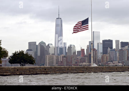 The American flag on Ellis Island at half-staff on a cloudy day with the Freedom Tower and skyline of Manhattan during the 13th anniversary of the 9/11 terrorist attacks September 11, 2014.