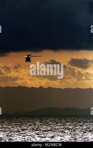 """010415-N-3400W-009LEYTE GULF  (April 15, 2001) -- At sunset a SH-60B assigned to the """"Chargers"""" of Helicopter Anti-Submarine Squadron One Four (HS-14) flies channel guard for USS Kitty Hawk (CV 63) as it passes through the Leyte straight. Kitty Hawk operates out of Yokosuka Naval Base, Japan, as the world's only forward-deployed aircraft carrier and is currently operating on a regularly scheduled deployment.  U.S. Navy Photo by Photographer's Mate 3rd Class Alex C. Witte (Released) 010415-N-3400W-009 by navalsafetycenter"""