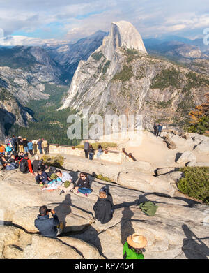 Half Dome Yosemite view from Glacier Point Overlook with people family taking pictures. Yosemite National Park California USA