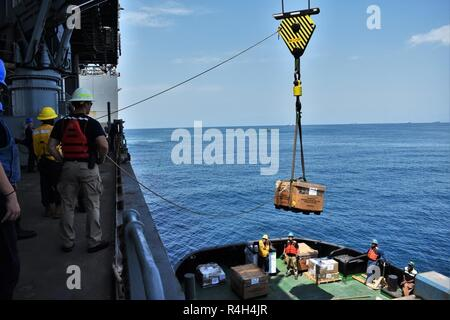 GULF OF ADEN (Sept. 29, 2018) USS Lewis B. Puller (ESB 3) crew conducts an onload of goods with a tugboat while forward deployed. The expeditionary sea base platform supports Naval Amphibious Force, Task Force 51, 5th Marine Expeditionary Brigade's diverse missions that include crisis response, airborne mine countermeasures, counter-piracy operations, maritime security operations and humanitarian aid/disaster relief missions while enabling TF 51/5 to extend its expeditionary presence in the world's most volatile regions.