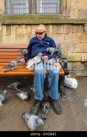 A man surrounded by Feral Pigeons as he feeds them breadcrumbs. He is sat on a city centre bench wearing wraparound sunglasses.