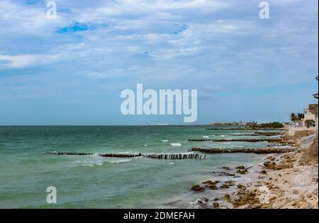 View along eroded beach with sand fencing in Progreso Mexico toward the worlds longest pier that allows ships to dock in the shallow Gulf of Mexico but also causes erosion of the beaches