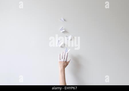 A hand half painted in white reaching for paper butterflies against white wall