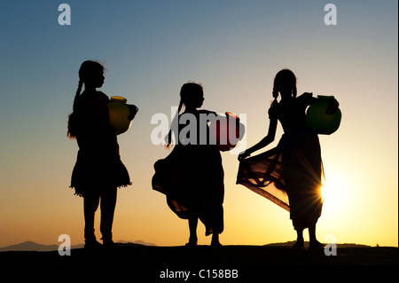 Rural Indian village girls with water pots at sunset. Silhouette. Andhra Pradesh, India
