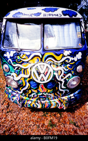 Hippie psychedelic paint job on VW Volkswagen split screen 1960s camper van on autumn fall leaves