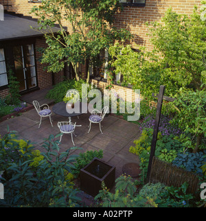 Birds-eye view of shady paved courtyard townhouse garden with small trees and circular table  with white chairs