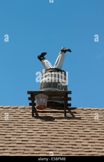 man-on-a-roof-upside-down-in-a-barrel-at