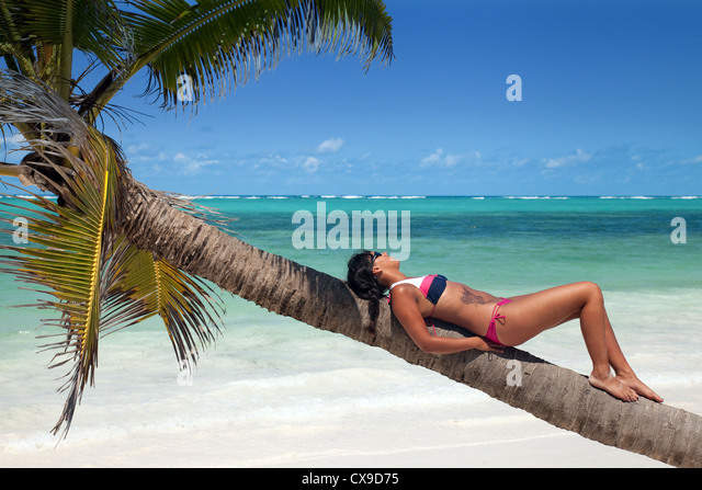 a-young-woman-sunbathing-on-a-palm-tree-