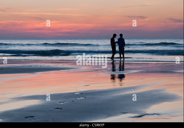 two-boys-fishing-in-the-sea-at-sunset-in