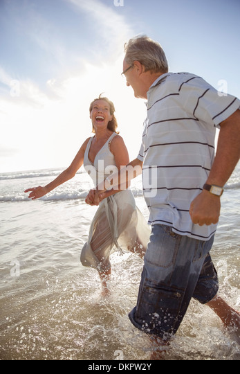 older-couple-playing-in-waves-on-beach-d