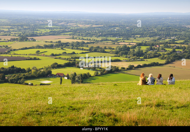 four-people-sitting-on-hillside-with-sou