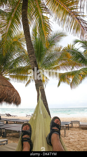 a-man-relaxing-in-a-hammock-on-the-beach