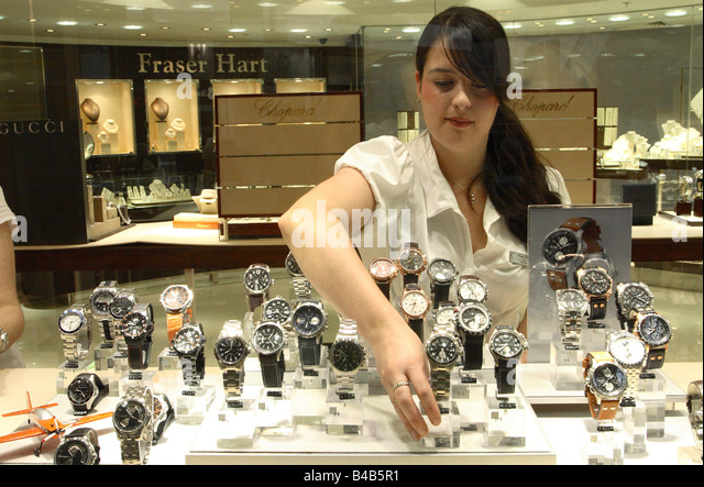 female-shop-assistant-placing-watches-in