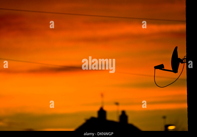 sky-tv-dish-and-house-roofs-in-silhouett