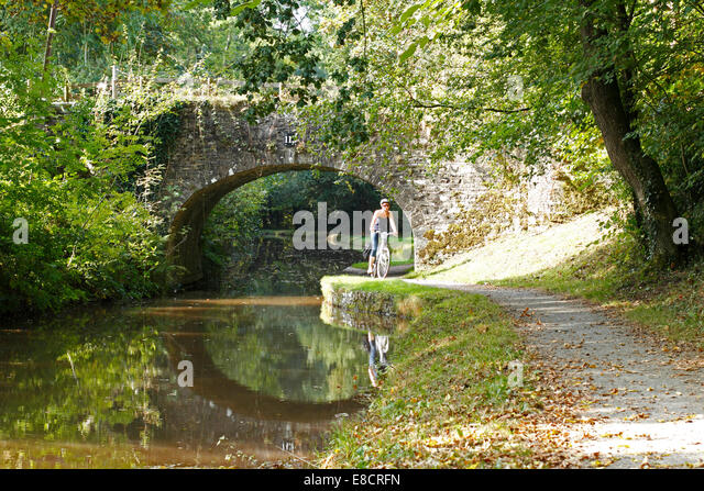 young-woman-cycling-along-a-canal-towpat