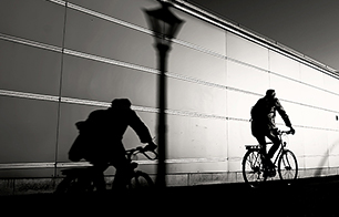 Man Riding Bicycle On Road By Wall - Stock Photo