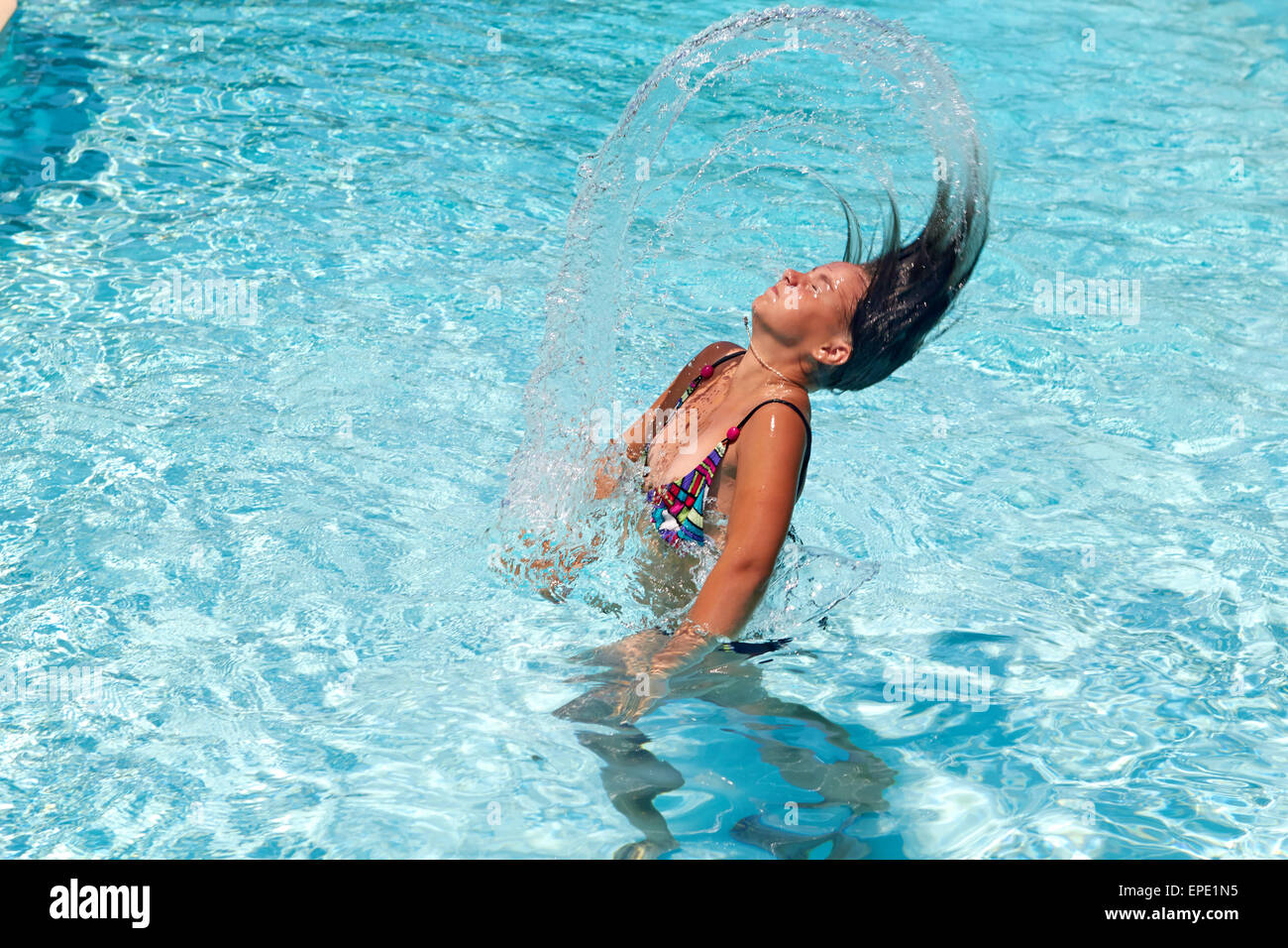 Pretty teen girl whipping her hair back in the pool and