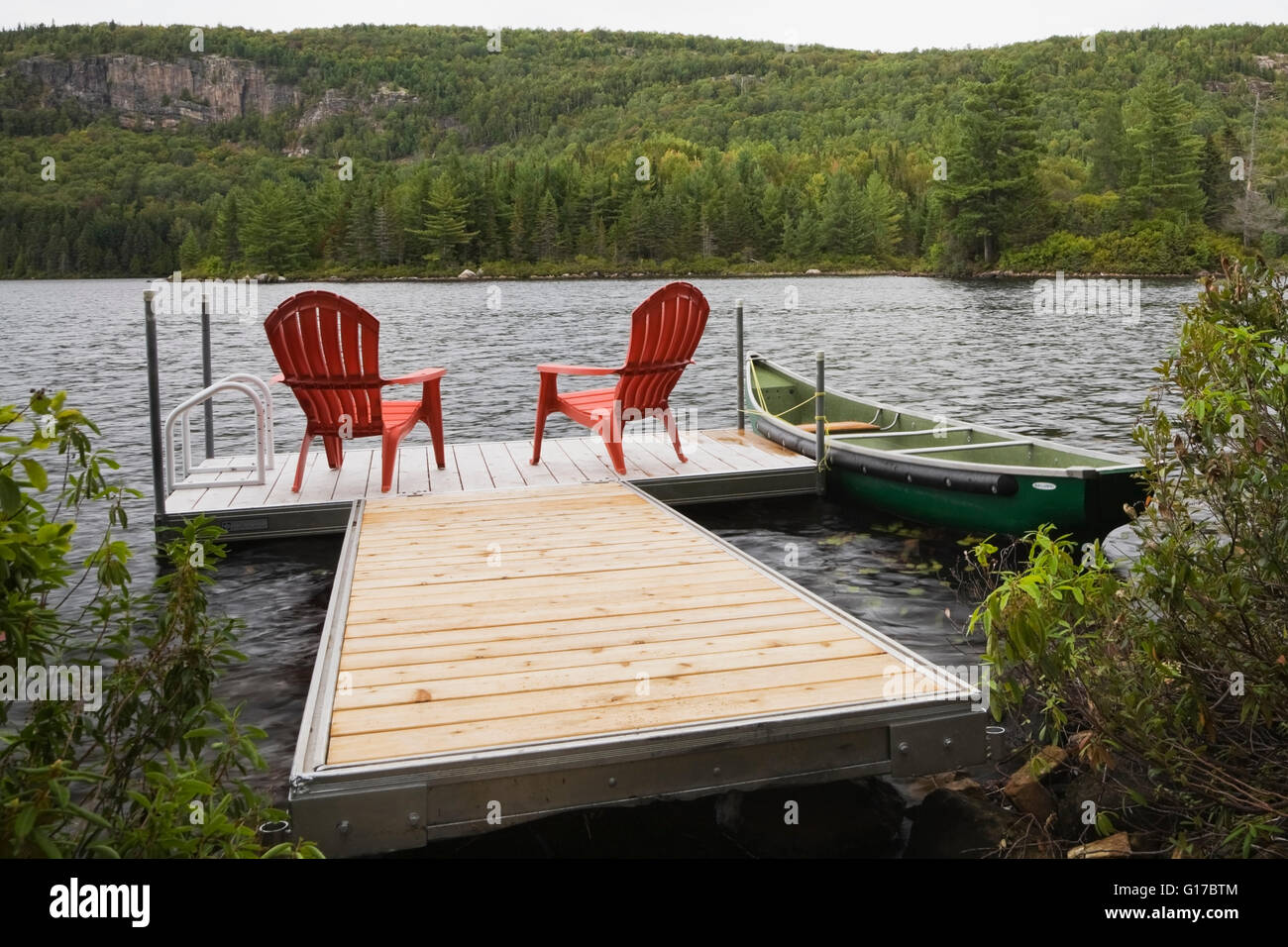 Two Red Adirondack Chairs On A Dock Stock Photo - Download