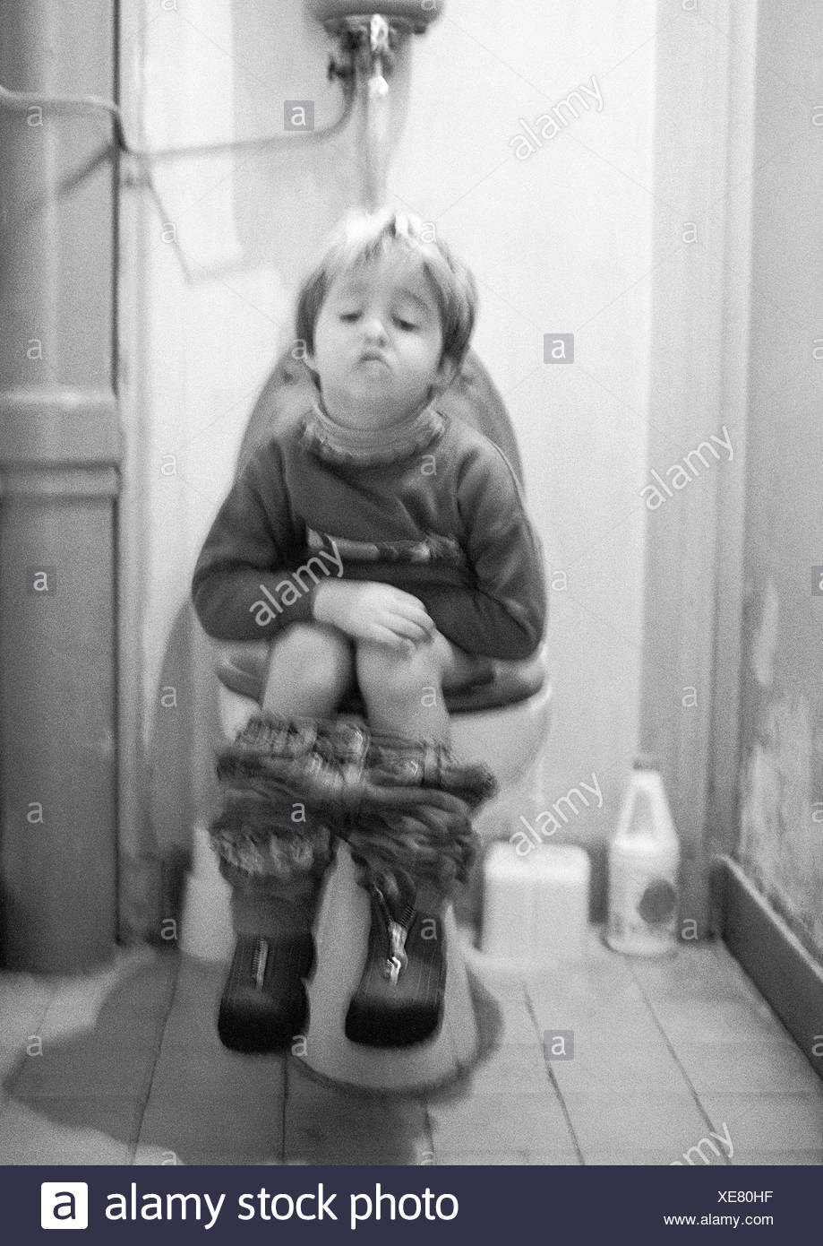 Little Girl With Tablet Sitting On The Toilet High-Res