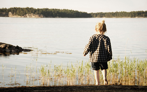 Little girl by the lake - Stock Photo