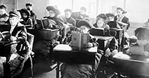 Children reading at desks in room of open air school, Providence - Stock Photo