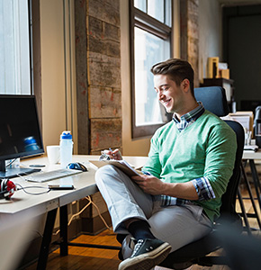 Entrepreneur making notes on clipboard in creative office space - Stock Photo