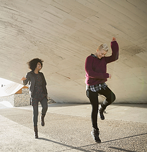 Female friends dancing under city bridge - Stock Photo