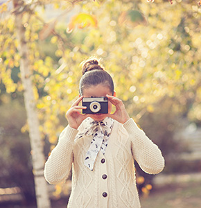 Hipster girl shooting on film camera outdoor - Stock Photo