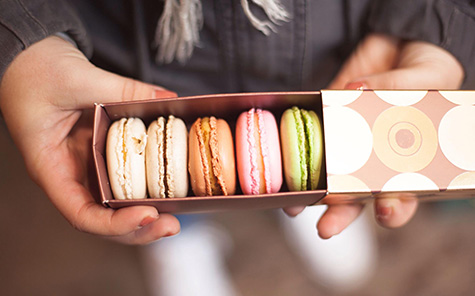Hands holding open box of multicolored macarons - Stock Photo