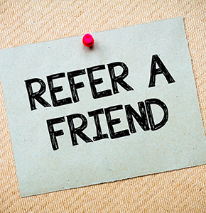 Recycled paper note pinned on cork board. Refer a Friend Message. Concept Image - Stock Photo