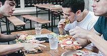 Dos estudiantes varones comiendo comida en el Café Foto de stock