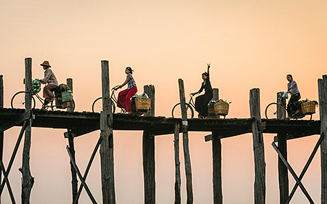 Burmese woman flashes peace sign on a bike riding over U Bein Bridge at sunset. U Bein Bridge Burma, Myanmar - Stock Photo