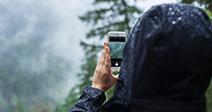 Woman taking photograph in the rain, BC, Canada - Stock Photo