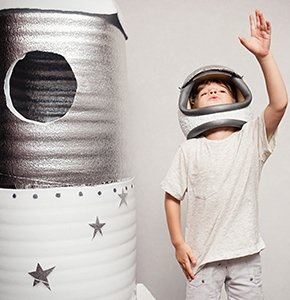 Happy child dressed in an astronaut costume playing with hand ma -  Stock Photo