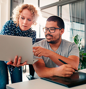 Portrait of young man sitting at his desk pointing at laptop in hands of a female colleague, male graphic designer - Stock Photo