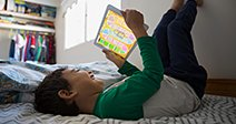 Boy feet up using digital tablet on bedStock Photo Stock Photo
