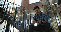 Businessman texting with cell phone in stairwell - Stock Photo