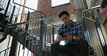 Geschäftsmann SMS mit Handy im Treppenhaus Stockfoto