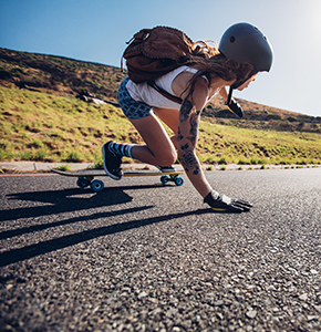 Young woman riding on her skateboard. Female skater practicing skating on country road. - Stock Photo