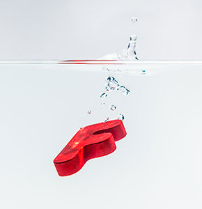 Red wooden alphabet F drop in the water with white background and selective focus - Stock Photo