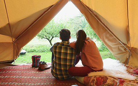 Young couple sitting in tent together. - Stock Photo