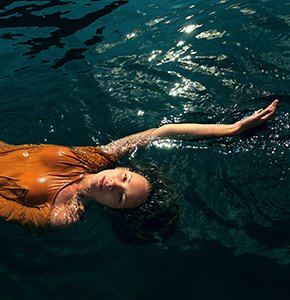 Girl swimming in the sea lying on water - Stock Photo