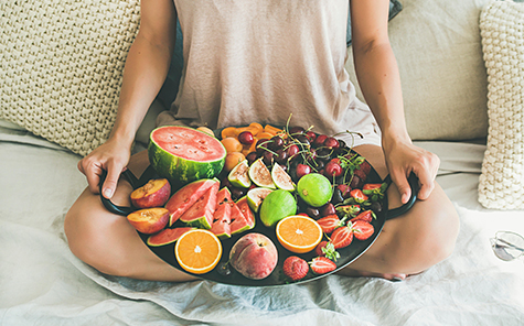 Summer healthy raw vegan clean eating breakfast in bed concept. Young girl wearing pastel colored home clothes sitting - Stock Photo