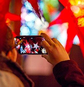 Ein Tourist nimmt ein Bild von Weihnachten Laternen an einem im Edinburgh Weihnachtsmarkt abgewürgt. Stock Foto