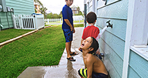 Boys rinsing off after swimming. Playing in water - Stock Photo