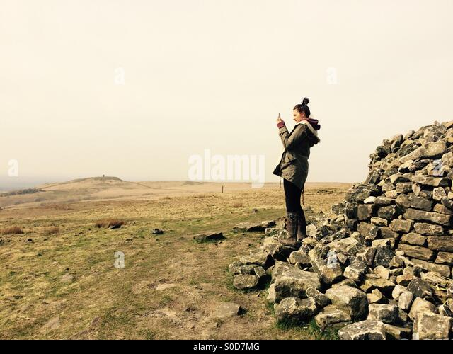 Girl taking photo with phone on hill summit